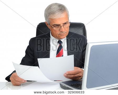Mature businessman at desk comparing note to laptop screen. Man is wearing eye glasses over a white background.