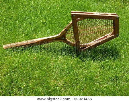Vintage tennis racket on grass court