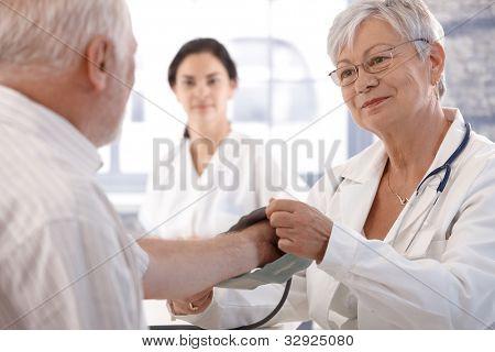Senior female doctor measuring old man's blood pressure.