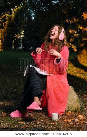 happy woman is laughing on magazine at forest in undress