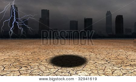 Dark city with hole in desert floor