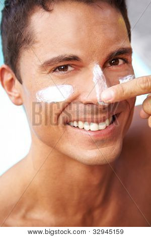 Happy smiling man putting sunscreen and suntan lotion on his face