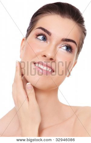Young beautiful smiling healthy woman touching her face, over white background