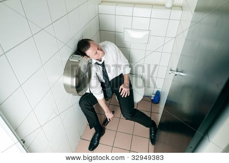 Young man is sitting drunk on a toilette, presumably he is in a club