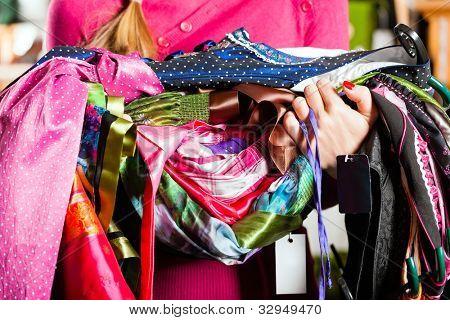 traditionelle Kleidung junge Frau ist Tracht oder Dirndl in einem Geschäft kaufen, sie hat viele Dirndl in er