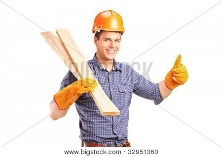 A smiling manual carpenter holding sills and giving thumb up isolated on white background