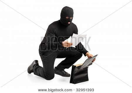 A thief reading a confidential documents after stealing a briefcase isolated on white background