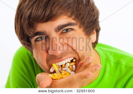 Young man is feeding himself pills and drugs, close-up