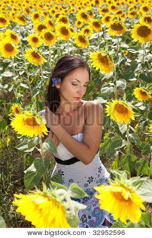 Hermosa morena teniendo cuidado de su pelo en un campo de girasol búlgaro