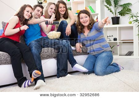 Friends looking something funny on TV and laughing, sitting in living room
