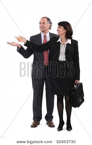 Mature businesscouple gesturing at blank copyspace