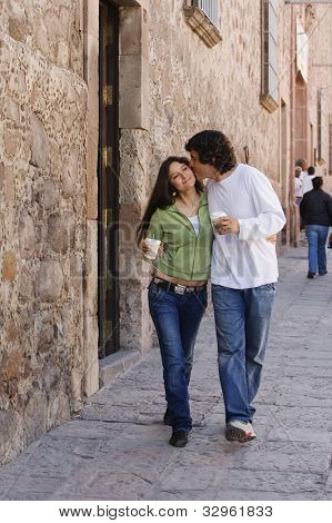 Hispanic couple with coffee on sidewalk