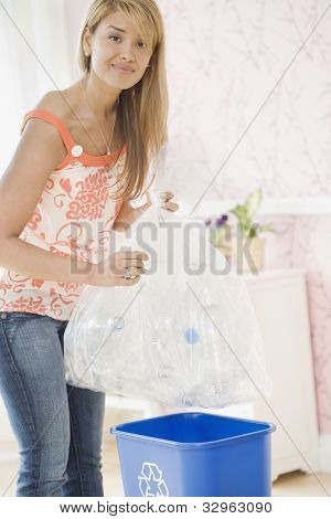 Hispanic woman filling recycling bin