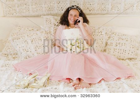 Hispanic girl on cell phone in Quinceanera dress