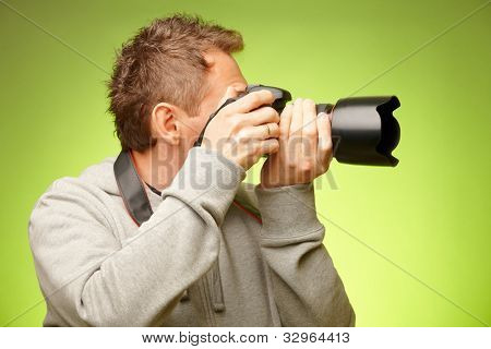 Male photographer taking photos with DSLR digital camera, side view