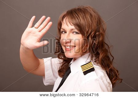 Beautiful woman pilot wearing uniform with epaulettes waving with her hand