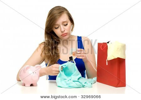 Unhappy woman with shopping bags and piggy bank