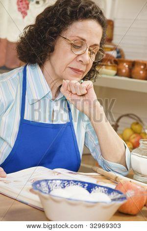 Senior Hispanic woman reading cook book