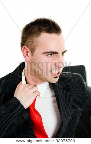 Stressed Young Businessman Yanking Necktie