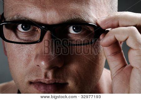 Portrait of a man adjusting his frames