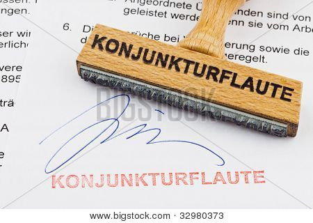 a stamp made of wood lying on a document. german words: economic downturn