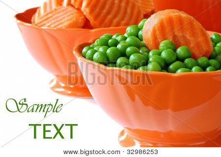 Freshly steamed peas and carrots in orange dishes on white background with copy space.  Macro with shallow dof.