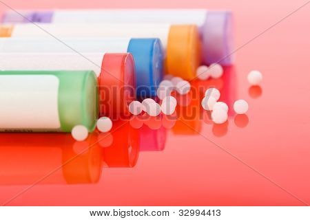 Colorful Homeopathic Pills And Containers On Red
