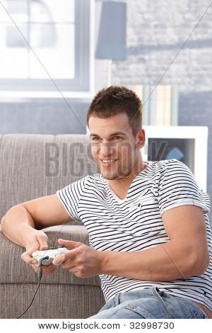 Young man sitting on floor at home, playing video gam, smiling.