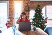 Beautiful woman sitting at the table working with laptop at home around christmas tree worried and s poster