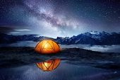 Camping Adventure In The Mountains. A Tent Pitched Up And Glowing Under The Milky Way. Photo Composi poster