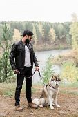Guy in casualwear holding leash of his purebred pet during chill in rural environment at leisure poster
