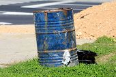 Heavily Used Rusted Dark Blue Metal Barrel Used At Local Construction Site Surrounded With Uncut Gra poster