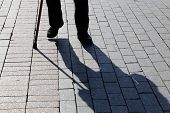 Shadow And Silhouette Of Limping Man Walking With A Cane On Pavement. Concept Of Disability, Old Age poster