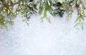 Christmas or winter background with a border of green and frosted evergreen branches on a grey vinta poster