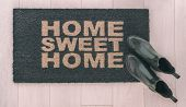 Home Sweet Home doormat entrance mat at front door of new condo in urban city living with stylish wo poster