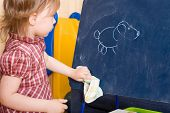 Постер, плакат: Маленькая девочка протирают рисунок на шифер таблетки