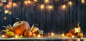 Thanksgiving - Pumpkins On Rustic Table With Candles And String Lights poster