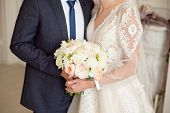 Wedding Bouquet Of Flowers In The Hand Of The Bride And Groom.bride In A Wedding Dress And Groom In  poster