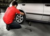 picture of car repair shop  - A male changing a tire on a car in a garage - JPG
