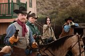 picture of hustler  - Cowgirl with three male companions in old American west scene - JPG