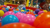 Happy Cute Girl Having Fun In Ball Pit In Kids Amusement Park And Indoor Play Center. Close Up Portr poster