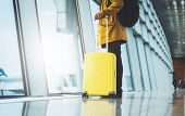 Traveler In Bright Jacket With Yellow Suitcase Backpack At Airport On Background Large Window Blue S poster
