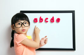picture of little school girl  - School girl wears a big spectacles posing next to a white board - JPG