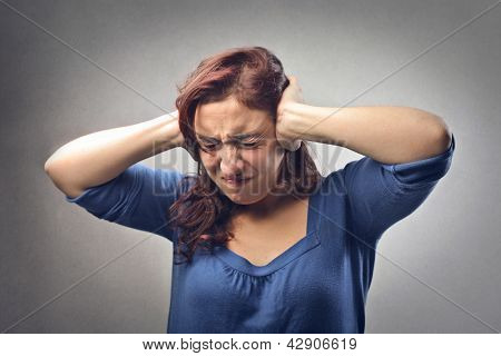 young woman covers her ears