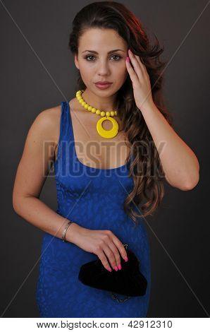Beautiful young brunette girl posing pretty to camera in the studio wearing short blue dress yellow