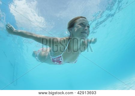 Young woman swimming underwater in a pool