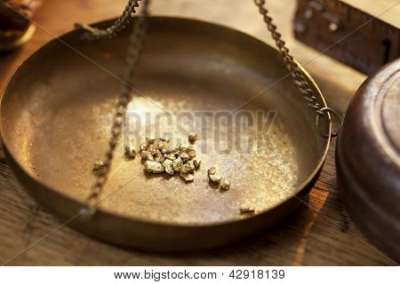 Weighing a gold nugget on a old brass scale dish for trade or exchange.