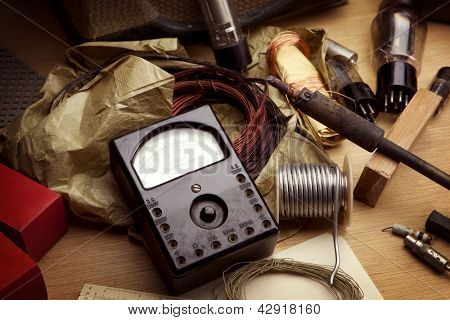 Vintage electronics. Vintage test meter and soldering equipment etc. Desk top of a retro 1960s - 1970s electrician, under incandescent light .