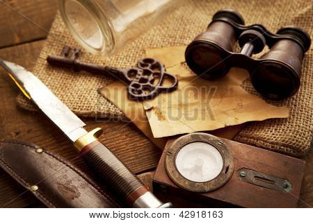 Treasure hunting setting, A compass, binoculars, knife and a old key on a old wooden desk