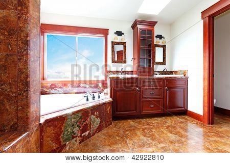 Baño casa nueva de lujo con mármol rojo y madera de caoba.